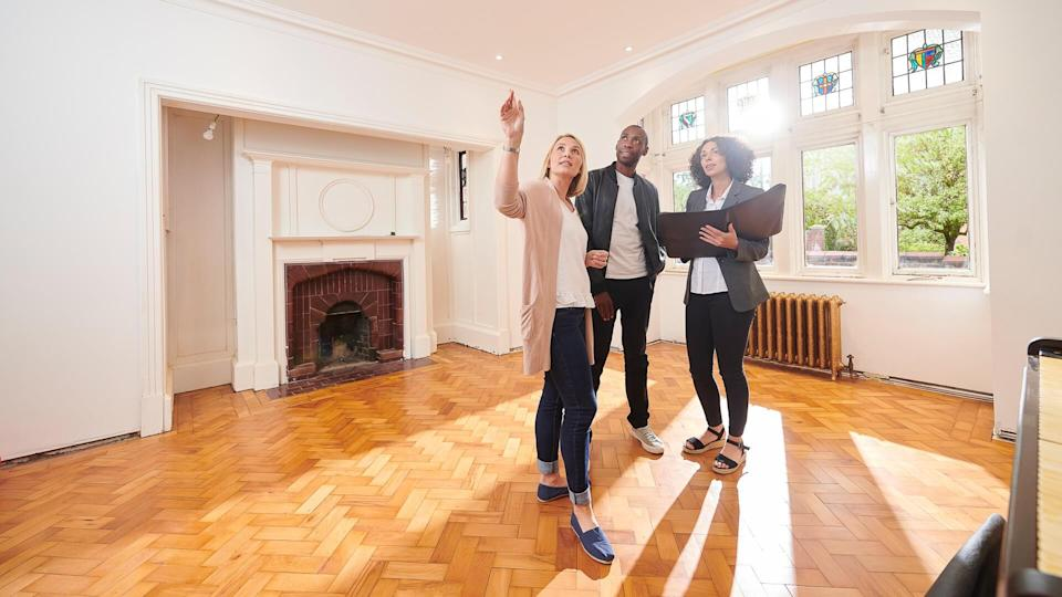 an estate agent shows a couple around a refurbished period home.