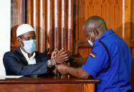 Mohamed Ahmed, a suspect charged with helping al Qaeda-linked militants to launch an attack on the Westgate mall, has his handcuffs removed as he sits in the dock during his sentencing, at the Milimani Law Courts in Nairobi