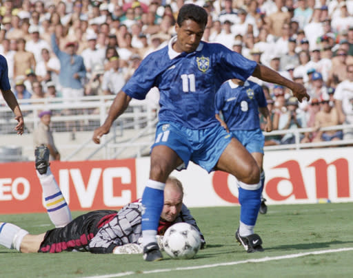 FILE - In this file photo dated July 13, 1994, Swedish goalie Thomas Ravelli watches Brazilian forward Romario dribble past him as Romario shoots at the goal during the World Cup soccer championship semifinal, Sweden vs. Brazil at the Rose Bowl in Pasadena, USA. The kick was saved on the line by Swedish defender Patrick Andersson (not in picture). The extrovert Sweden goalkeeper Ravelli who helped give the Scandinavian nation one of its greatest sporting rushes when the Sweden team reached the semifinals of the 1994 World Cup in the United States, and Sweden's national TV broadcaster plans Friday April 10, 2020, to replay the team's games over the coming weeks in an attempt to unite the nation during the coronavirus pandemic. (AP Photo/Thomas Kienzle, FILE)