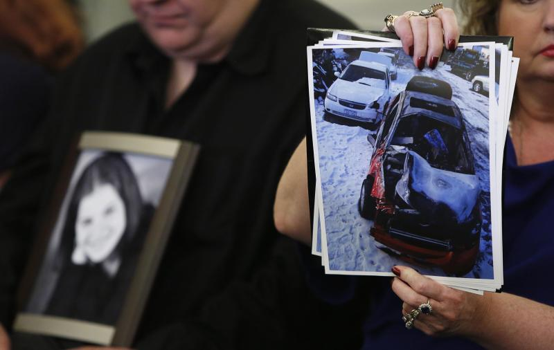 Surviving family member Leo holds a photo of his deceased daughter Kelly as his wife Mary Theresa holds up photos of Kelly's wrecked 2005 Chevrolet Cobalt, before start of Senate subcommittee in Washington