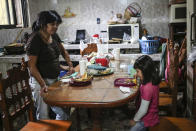 Elisa Xolalpa, who survived an acid attack while tied to a post by her ex-partner 20 years ago when she was 18, waits for her six-year-old daughter Monserrat to finish lunch in the kitchen of Elisa's parents' home in Mexico City, Sunday, July 4, 2021. Xolalpa recognizes that one day she will have to explain to her three daughters, product of another relationship, the attack that changed her life and for a time left her wanting to die. (AP Photo/Ginnette Riquelme)