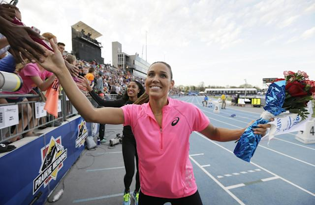Lolo Jones reacts with fans after running in the women's special shuttle hurdle relay at the Drake Relays athletics meet, Friday, April 25, 2014, in Des Moines, Iowa. (AP Photo/Charlie Neibergall)