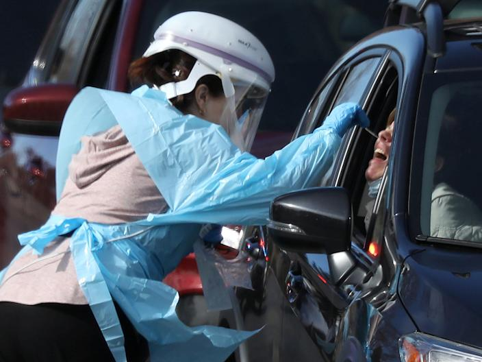 A healthcare worker tests people at a drive-thru testing station run by the state health department, for people who suspect they have coronavirus, in Denver, Colorado, March 11, 2020.