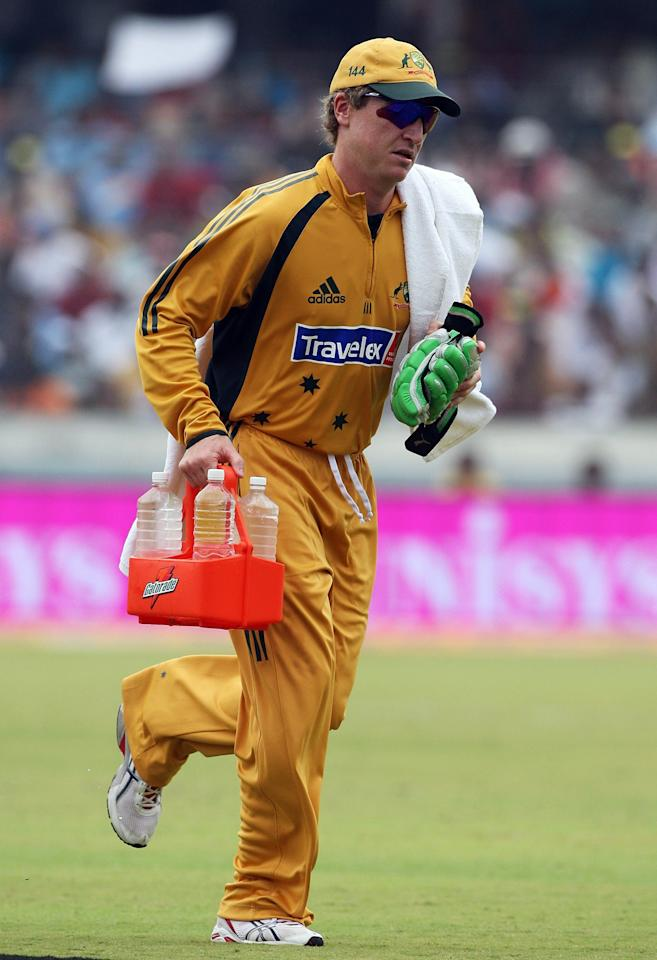 HYDERABAD, INDIA - OCTOBER 05:  Brad Haddin of Australia runs some drinks from the field during the third one day international match between India and Australia at the Rajiv Gandhi International Cricket Stadium on October 5, 2007 in Hyderabad, India.  (Photo by Hamish Blair/Getty Images)