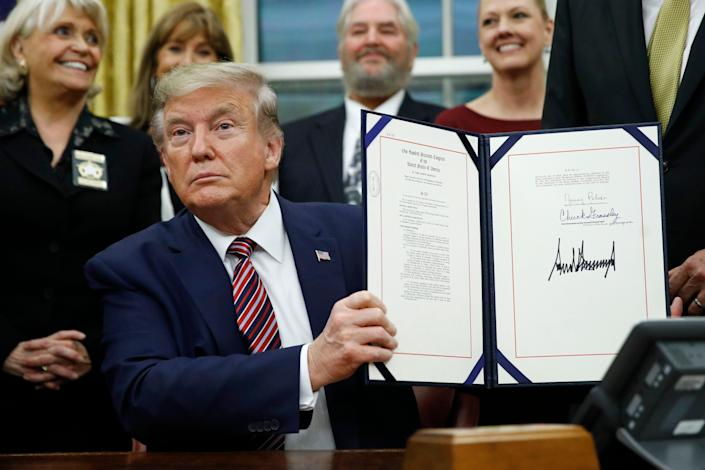 President Donald Trump displays the Preventing Animal Cruelty and Torture Act after signing it during a ceremony Nov. 25, 2019.