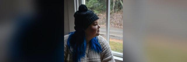 photo of author in a green hat with her blue hair out, looking outside the window. Wearing a pale sweater