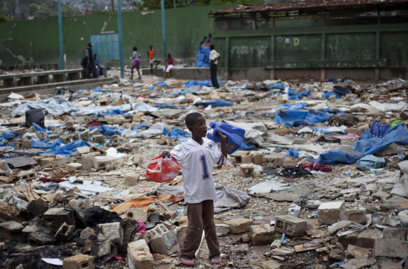 """A youth searches for recoverable items left behind by people evicted from the camp that had been set up for people displaced by the 2010 earthquake near the national stadium in Port-au-Prince, Haiti, Monday, April 22, 2013. Haitian Prime Minister Laurent Lamothe told The Associated Press Monday night that there were """"some"""" landowners who were responsible for forced evictions but it was not something the government endorsed.  A report by the global advocacy group Amnesty International says forced evictions violate the rights of displaced people at all stages: threats prior to an eviction, violence during eviction and homelessness afterward, and that Haiti has violated international human rights obligations by failing to protect displaced people. (AP Photo/Dieu Nalio Chery)"""