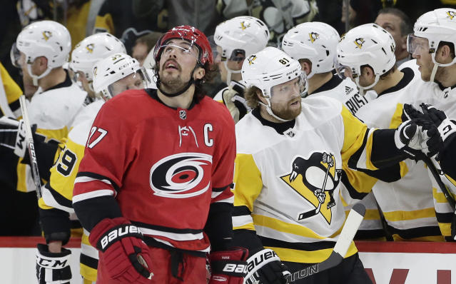 Carolina Hurricanes' Justin Faulk (27) looks at the scoreboard as Pittsburgh Penguins' Phil Kessel (81) is congratulated following Kessel's goal during the second period of an NHL hockey game in Raleigh, N.C., Friday, Feb. 23, 2018. (AP Photo/Gerry Broome)