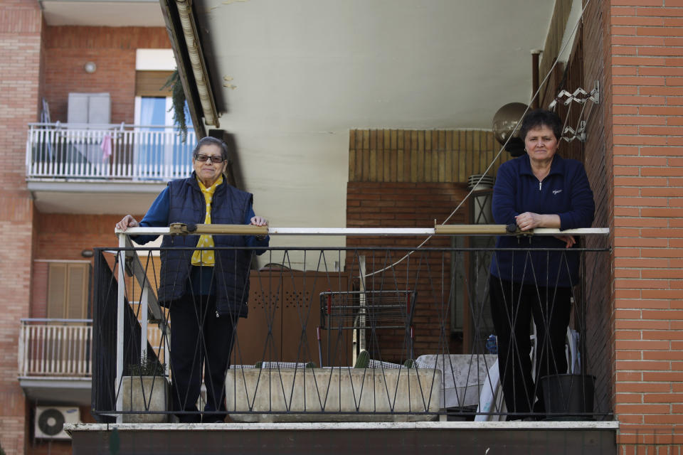 In this March 11, 2020, photo, Agnese Grosso, left, 85, poses for a photo flanked by her caregiver Murario Aspazzia, at the balcony of his home in Rome. Italy has one of the world's oldest populations, and the coronavirus outbreak is taking its toll on family relationships. The elderly are sealing themselves off from loved ones or can't be visited due to nursing home rules or travel restrictions. (AP Photo/Alessandra Tarantino)