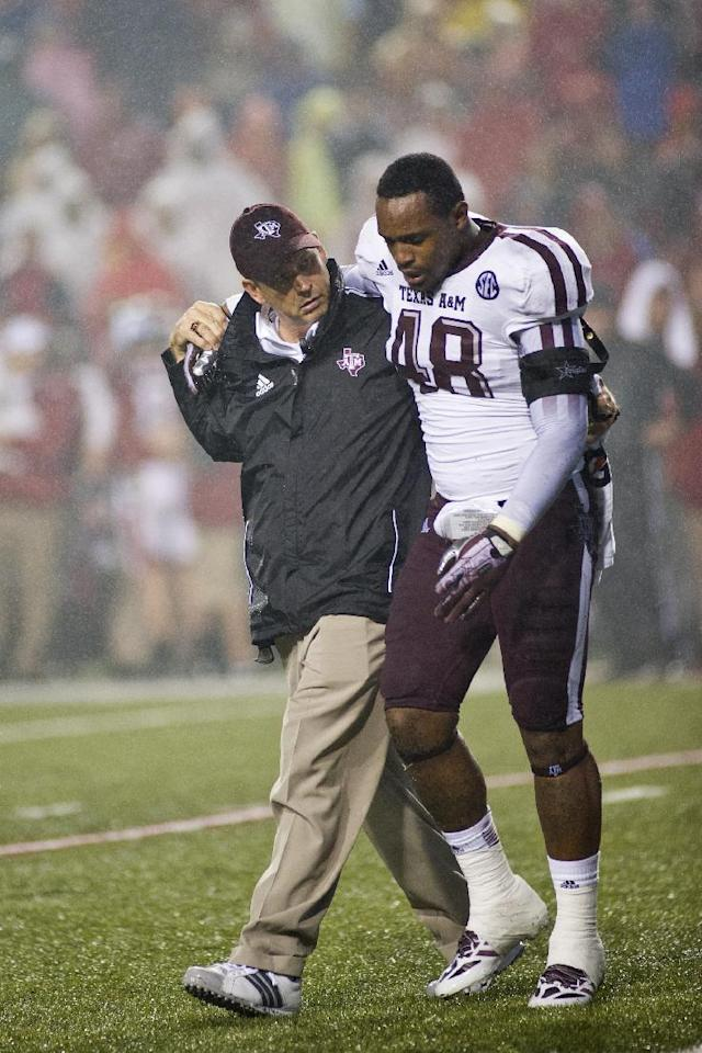 Texas A&M linebacker Darian Claiborne (48) is helped off the field during an NCAA college football game against the Arkansas Razorbacks in Fayetteville, Ark., Saturday, Sept. 28, 2013. Texas A&M defeated Arkansas 45-33. (AP Photo/Beth Hall)