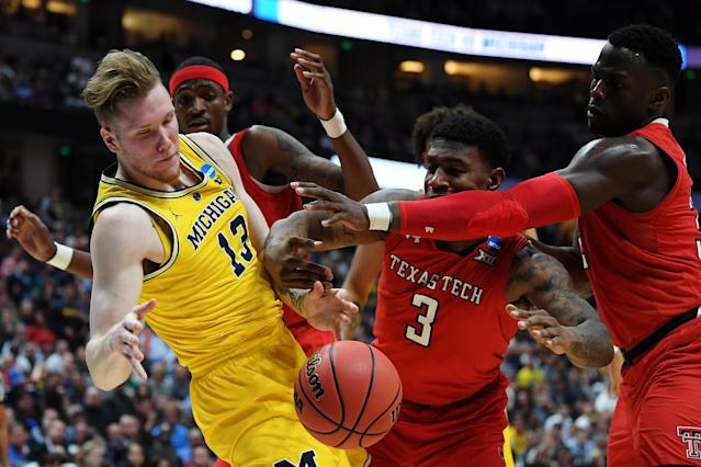 <p>Ignas Brazdeikis #13 of the Michigan Wolverines fights for the ball against DeShawn Corprew #3 and Norense Odiase #32 of the Texas Tech Red Raiders during the 2019 NCAA Men's Basketball Tournament West Regional at Honda Center on March 28, 2019 in Anaheim, California. (Photo by Harry How/Getty Images) </p>