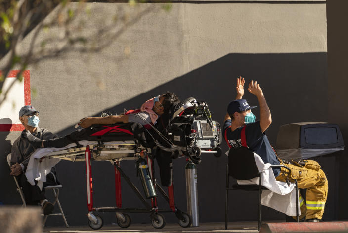 """An unidentified patient receives oxygen on a stretcher, while Los Angeles Fire Department Paramedics monitor him outside the Emergency entrance, waiting for a room at the CHA Hollywood Presbyterian Medical Center in Los Angeles Friday, Dec. 18, 2020. Increasingly desperate California hospitals are being """"crushed"""" by soaring coronavirus infections, with one Los Angeles emergency doctor predicting that rationing of care is imminent. (AP Photo/Damian Dovarganes)"""