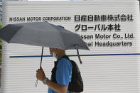 A man walks past Nissan Motor Co.'s global headquarters in Yokohama, near Tokyo, Tuesday, June 22, 2021. Nissan Chief Executive Makoto Uchida pleaded for patience from disgruntled shareholders Tuesday, promising a turnaround at the Japanese automaker, which is projecting a third year of losses as it struggles to distance itself from a scandal over its former Chairman Carlos Ghosn. (AP Photo/Koji Sasahara)