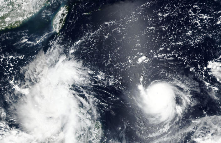 This Sept, 8, 2021, satellite image released by NASA shows Typhoon Chanthu, right, developing from a tropical depression into a powerful typhoon moving towards Taiwan, top left, as the remanence of Typhoon Conson, left, covers the Philippines. Chanthu continues gaining strength and is expected to make landfall in Taiwan over the weekend. (NASA Worldview, Earth Observing System Data and Information System (EOSDIS) via AP)