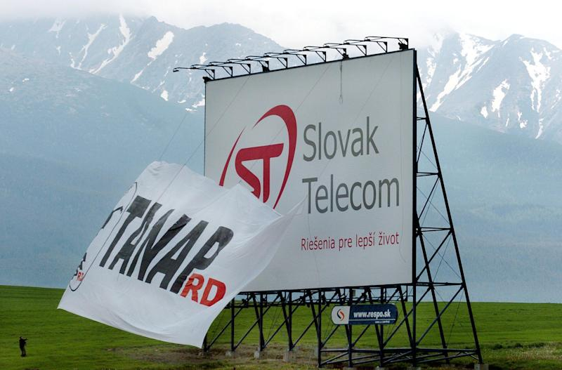 Slovak enviromental activists cover a controversial Slovak Telecom advertising billboard near the High Tatra Mountains at Vazec on June 4, 2004