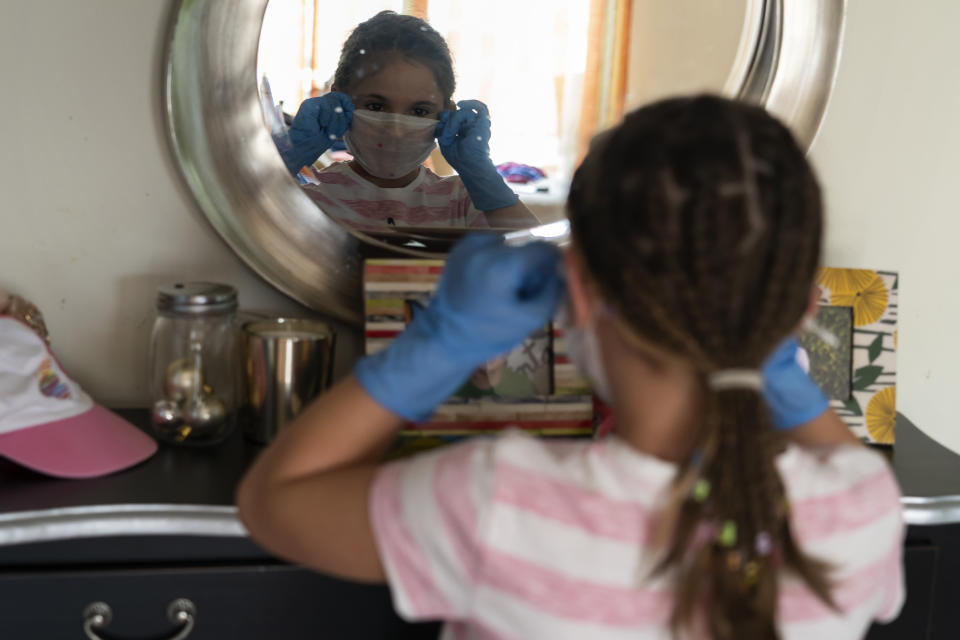 A girl adjusts her mask before going out on the street for the first time after 42 days of confinement during the mandatory quarantine decreed by the government as a result of the coronavirus (Covid-19) in Santander, Spain on April 26, 2020.  (Photo by Joaquin Gomez Sastre/NurPhoto via Getty Images)
