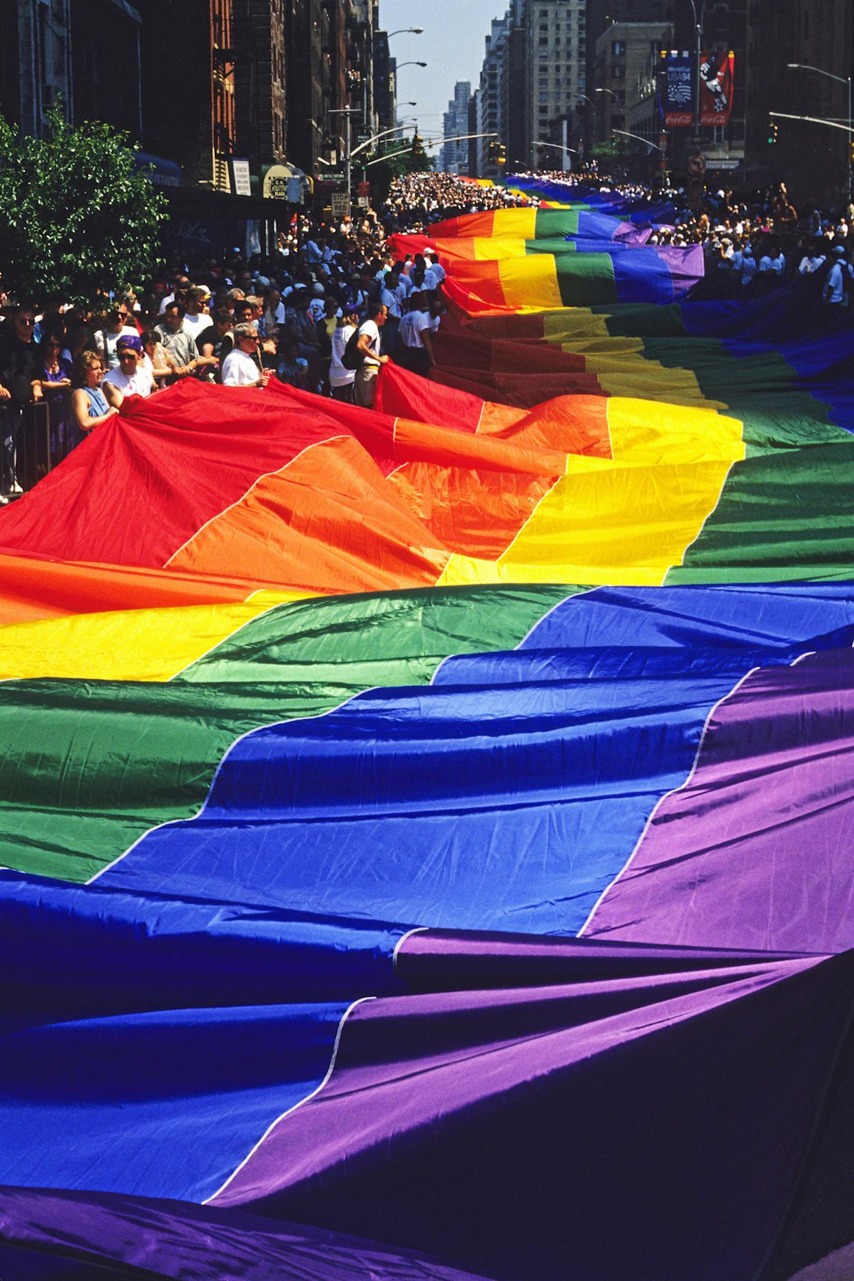 Hundreds of marchers carrying a rainbow flag at the Gay Pride Parade, commemorating the 25th anniversary of the Stonewall police raid in Greenwich Village. (Photo by ANDREW HOLBROOKE/Corbis via Getty Images)