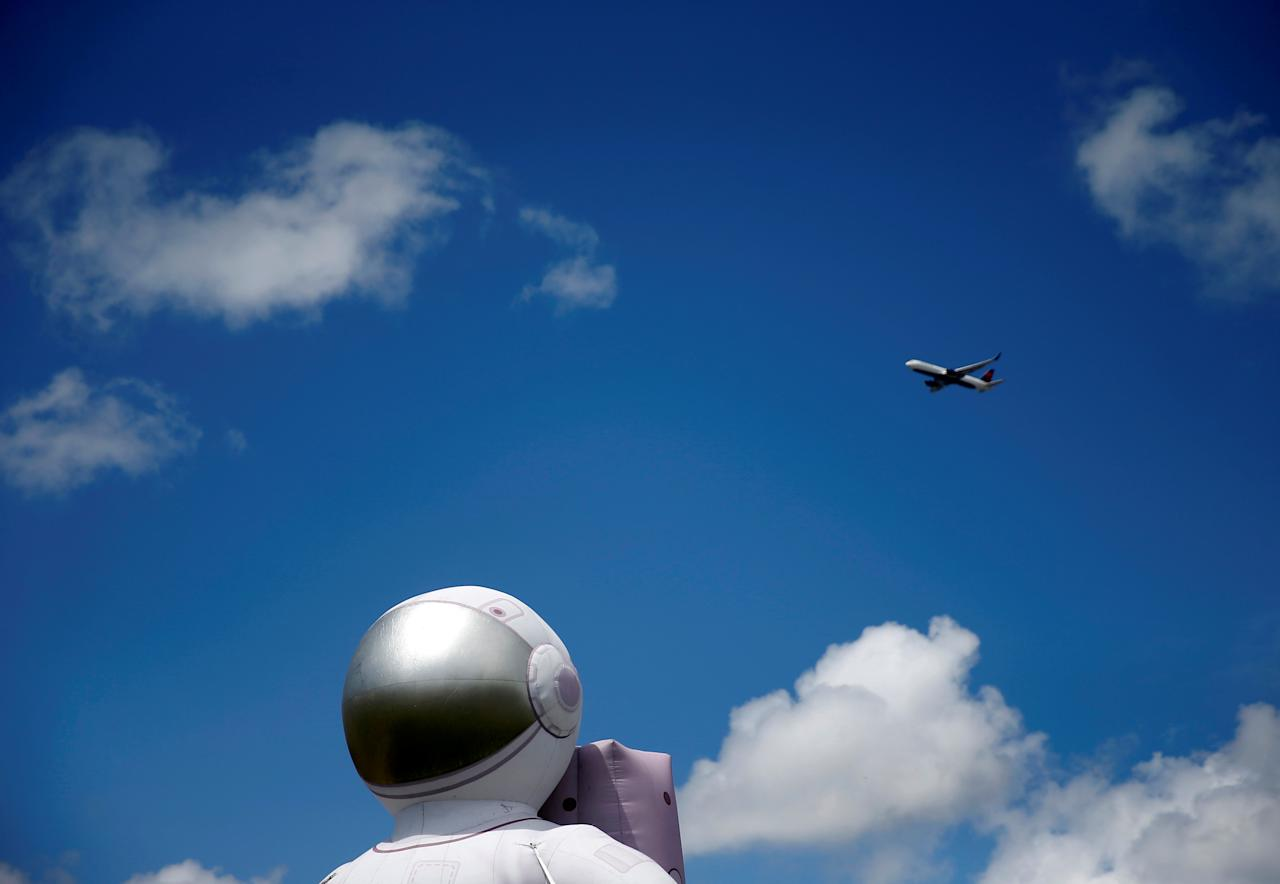 A plane passes by a large inflated astronaut outside the Museum of Flight on the anniversary of the Apollo 11 mission launch in Seattle, Washington, U.S., July 16, 2019.   REUTERS/Lindsey Wasson     TPX IMAGES OF THE DAY