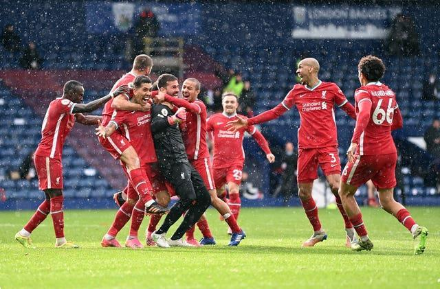 Liverpool players celebrate with goalkeeper Alisson Becker after he scored the winner at West Brom
