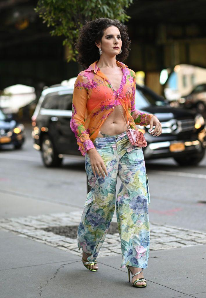 <p>Hari Nef wears a sheer shirt and floral trousers to the Collina Strada show.</p>
