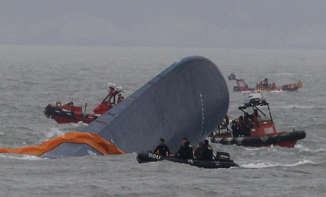 South Korean Coast Guard officers search for missing passengers aboard a sunken ferry in the water off the southern coast near Jindo, South Korea, Thursday, April 17, 2014. Strong currents, rain and bad visibility hampered an increasingly anxious search Thursday for more than 280 passengers still missing a day after their ferry flipped onto its side and sank in cold waters off the southern coast of South Korea.(AP Photo/Ahn Young-joon)