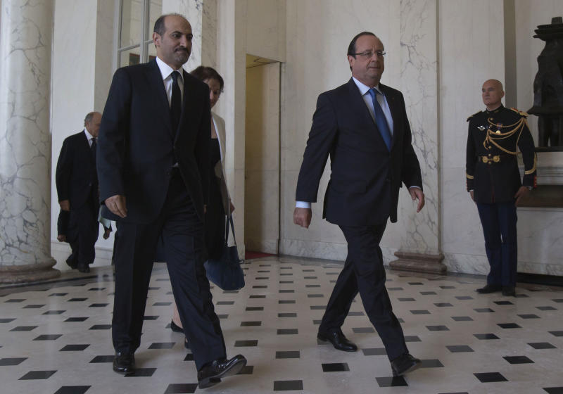 Head of the Syrian National Coalition, Ahmad al-Jarba, left, and France's President Francois Hollande walk in the lobby of the Elysee Palace Thursday Aug. 29, 2013. (AP Photo/Michel Euler, Pool)