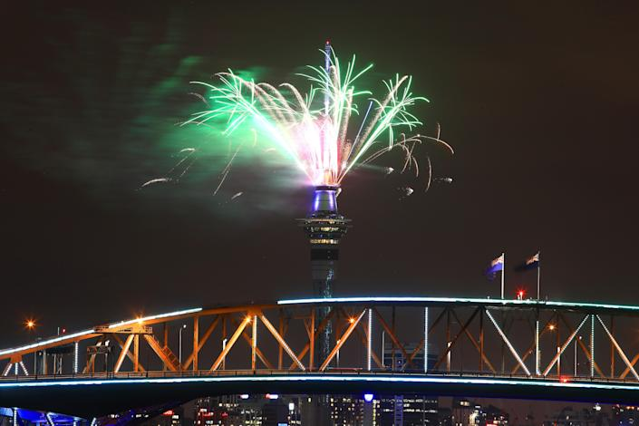 Fireworks explode from the Sky Tower with the Auckland Harbour Bridge. (Photo: Phil Walter/Getty Images for ATEED)