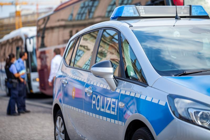 German police car stands on street. Two police officers controls traffic. Polizei is the german word for police