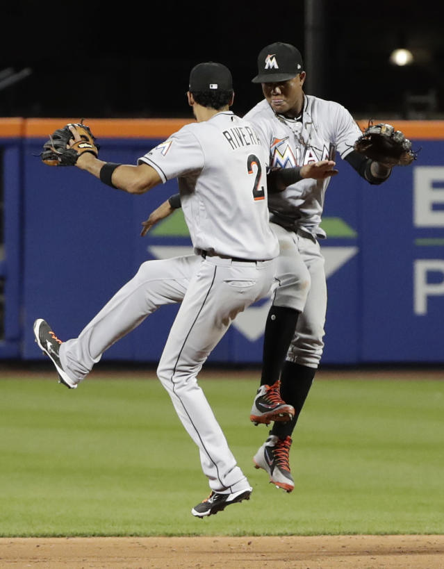 Miami Marlins' Starlin Castro, right, celebrates with teammate Yadiel Rivera, left, after a baseball game against the New York Mets Wednesday, May 23, 2018, in New York. The Marlins won 2-1. (AP Photo/Frank Franklin II)