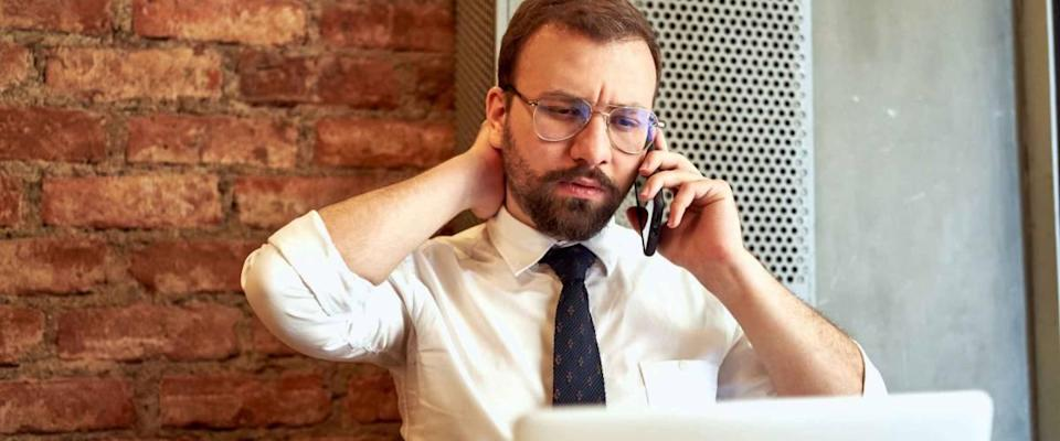 Man in white shirt and tie, stressed out on the phone.