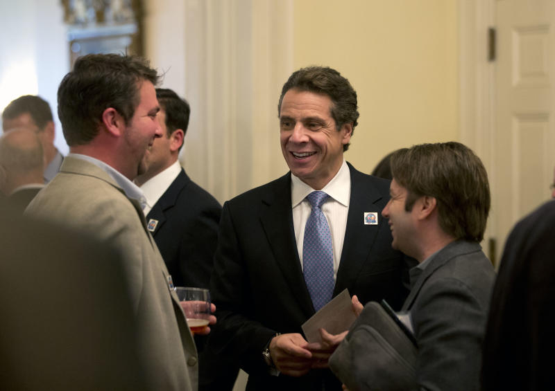 """New York Gov. Andrew Cuomo, left, talks to visitors to the Executive Mansion as part of a """"Wine, Beer and Spirits Summit"""" on Wednesday, Oct. 24, 2012, in Albany, N.Y. The aim of the summit is to boost wine production and craft brewers, in part to spur job growth. Visitors to the mansion were able to sample products from around New York state. (AP Photo/Mike Groll)"""