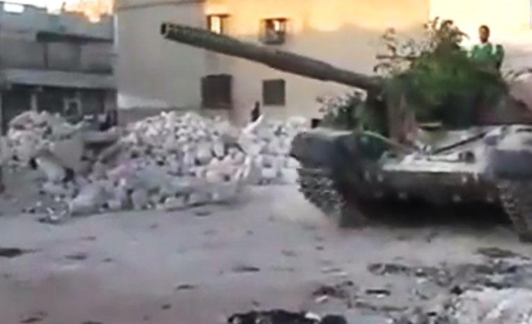 In this image made from amateur video released by the Ugarit News and accessed Tuesday, July 24, 2012, a Free Syrian Army solider drives a Syrian military tank in Aleppo, Syria. (AP Photo/Ugarit News via AP video) TV OUT, THE ASSOCIATED PRESS CANNOT INDEPENDENTLY VERIFY THE CONTENT, DATE, LOCATION OR AUTHENTICITY OF THIS MATERIAL