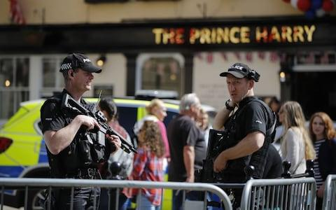 Armed British police officers patrol near The Prince Harry pub in Windsor - Credit: TOLGA AKMEN /AFP