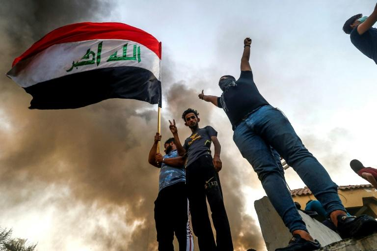Iraqi protesters wave the national flag in the southern city of Basra on September 7, 2018