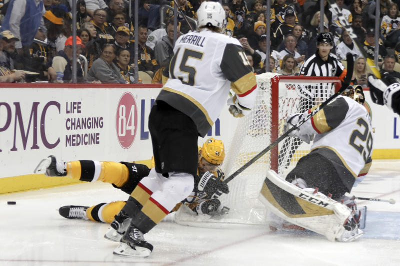 Pittsburgh Penguins' Zach Aston-Reese, bottom left, slides past Vegas Golden Knights goaltender Marc-Andre Fleury (29) as his stick hits Fleury during the second period of an NHL hockey game, Saturday, Oct. 19, 2019, in Pittsburgh. Aston-Reese was penalized for goaltender interference. Golden Knights' Jon Merrill (15) looks on. (AP Photo/Keith Srakocic)