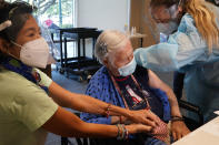Patricia Wasseman, holds Hermina Levin's hands as nurse Eva Diaz administers the Pfizer vaccine at John Knox Village, Wednesday, Dec. 16, 2020, in Pompano Beach, Fla. Nursing home residents and health care workers in Florida began receiving the Pfizer vaccine this week. (AP Photo/Marta Lavandier)