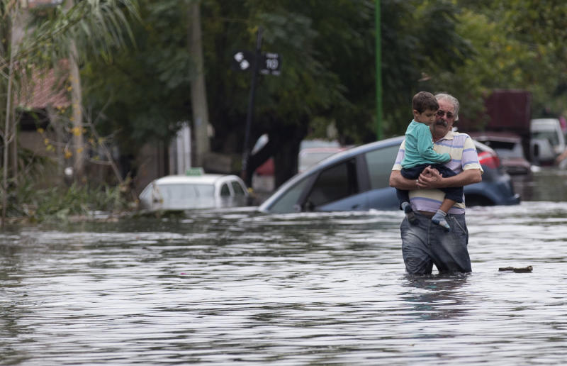 A man with a boy in his arms wades through a flooded street in La Plata, in Argentina's Buenos Aires province, Wednesday, April 3, 2013. At least 35 people were killed by flooding overnight in Argentina's Buenos Aires province, the governor said Wednesday, bringing the overall death toll from days of torrential rains to at least 41 and leaving large stretches of the provincial capital under water. (AP Photo/Natacha Pisarenko)