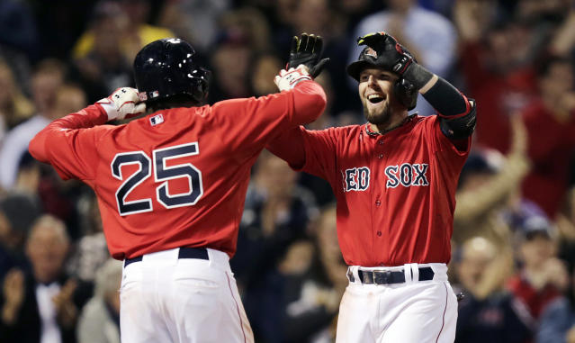 Boston Red Sox's Dustin Pedroia is congratulated by teammate Jackie Bradley Jr. (25) after his grand slam off Oakland Athletics relief pitcher Ryan Cook during the sixth inning of a baseball game at Fenway Park in Boston, Friday, May 2, 2014. (AP Photo/Charles Krupa)