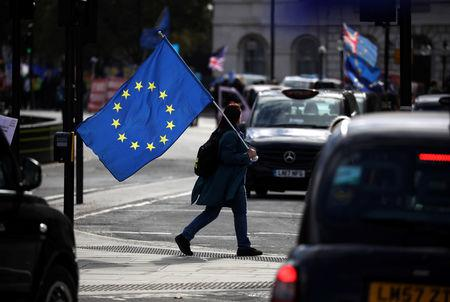 An Anti-Brexit protester crosses the street outside the Houses of Parliament, in Westminster