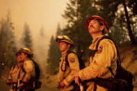 Cal Fire Capt. Dom Kaska, right, monitors flames as his crew burns vegetation to stop the Dixie Fire from spreading near Prattville in Plumas County, Calif., on Friday, July 23, 2021. (AP Photo/Noah Berger)