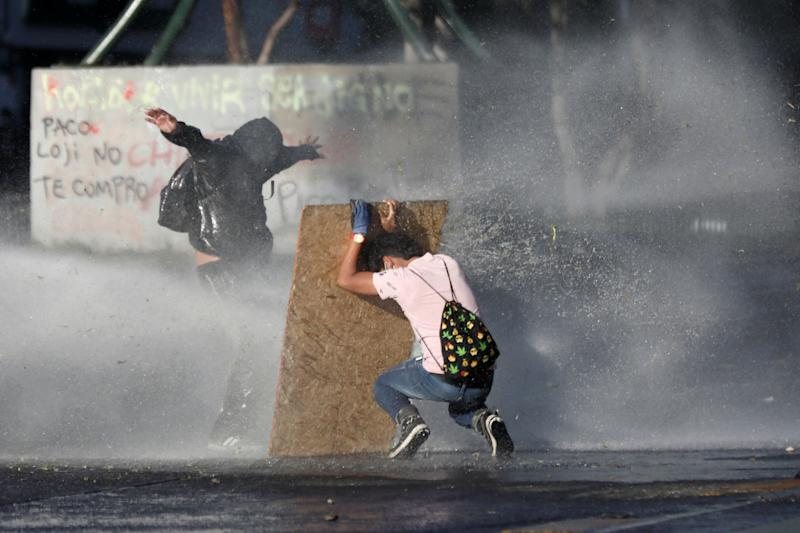 Demonstrators react as police water cannon is deployed during a protest against Chile's state economic model in Santiago, Chile on Oct. 28, 2019. (Photo: Edgard Garrido/Reuters)