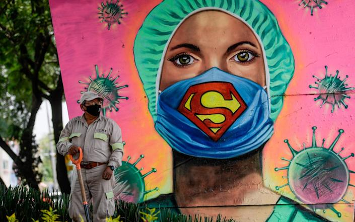 A city gardener works next to a mural showing a health worker wearing a Superman face mask - Pedro Pardo/AFP