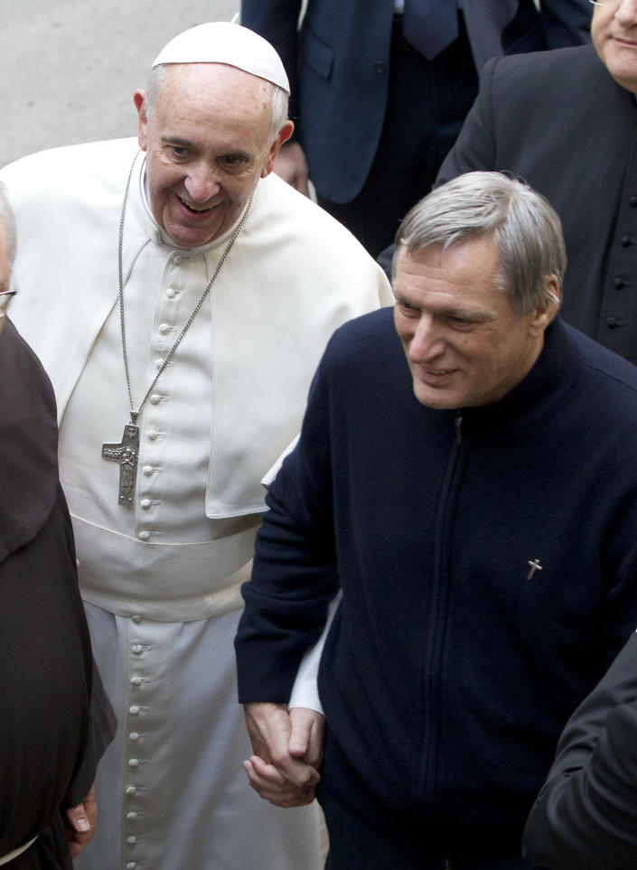 Pope Francis, holds hands with Don Luigi Ciotti as he arrives for a meeting with relatives of innocent mafia victims, in Rome's St. Gregorio VII church, just outside the Vatican, Friday, March 21, 2014. (AP Photo/Andrew Medichini)