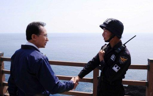 South Korean President Lee Myung-Bak shakes hands with a police guard during a visit to the disputed islands