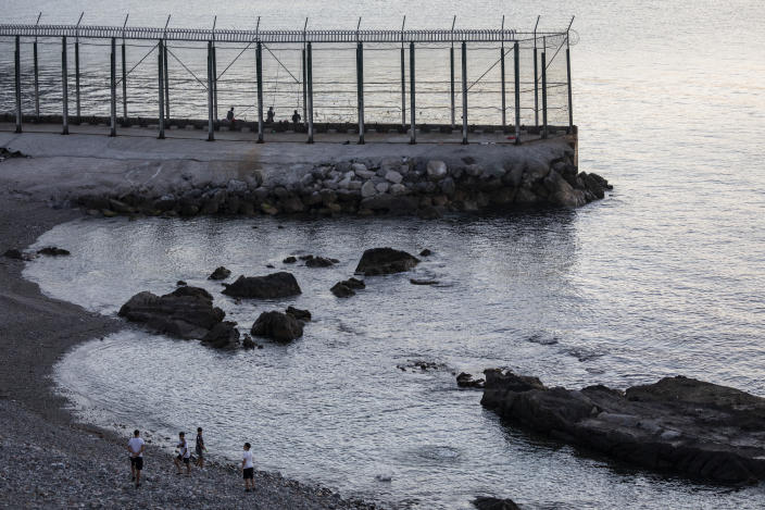 Spanish children play on the beach near the border fence separating Spain and Morocco in the district of Benzu, Spanish enclave of Ceuta, Thursday, June 3, 2021. (AP Photo/Bernat Armangue)