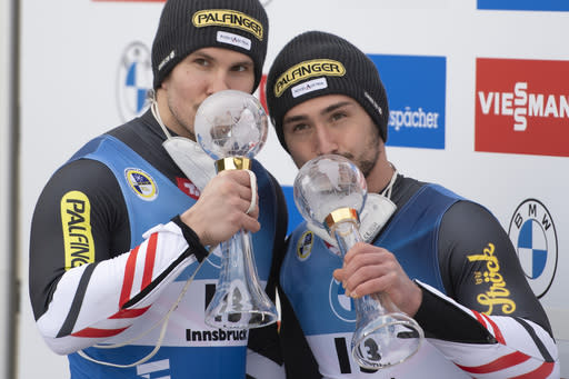 Thomas Steu, left, and Lorenz Koller of Austria kiss their trophys for winning the sprint world cup during the victory ceremony for the men's doubles sprint race at the Luge World Cup event in Innsbruck, Austria, Sunday, Jan. 24, 2021. (AP Photo/Andreas Schaad)