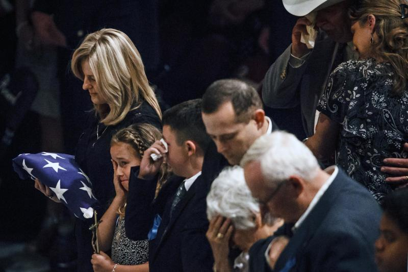 Donna Bachmann, left to right, holds a flag draped over her husbands coffin as her daughter Caitlyn and son Colby react during the funeral service for her husband Brazos County Precinct 1 Constable Brian Bachmann at Reed Arena on the Texas A&M University Campus, Saturday, Aug. 18, 2012, in College Station, Texas. Bachmann was fatally shot while trying to serve a court summons for being two months behind on rent. (AP Photo/Houston Chronicle, Michael Paulsen) MANDATORY CREDIT: MICHAEL PAULSEN/HOUSTON CHRONICLE
