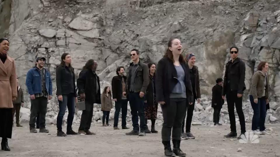 A large group of people stand outside in a rock quarry