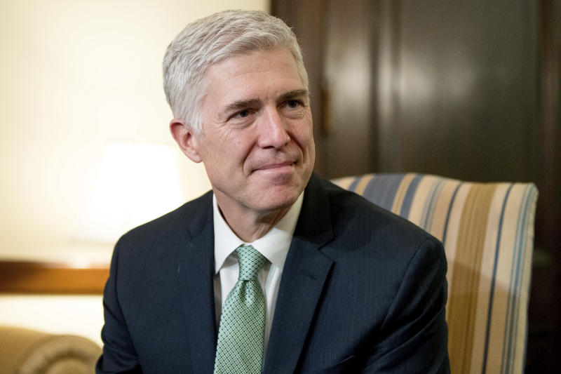 """<p> FILE - In this Feb. 14, 2017, file photo, Supreme Court Justice nominee Neil Gorsuch meets with Sen. Chris Coons, D-Del. on Capitol Hill in Washington. Gorsuch is roundly described by colleagues and friends as a silver-haired combination of wicked smarts, down-to-earth modesty, disarming warmth and careful deliberation. His critics largely agree with that view of the self-described """"workaday judge"""" in polyester robes. Even so, they're not sure it's enough to warrant giving him a spot on the court. (AP Photo/Andrew Harnik, File) </p>"""