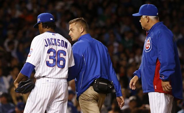 Chicago Cubs starting pitcher Edwin Jackson (36) leaves a baseball game with head trainer PJ Mainville as manager Rick Renteria, right, watches during the sixth inning against the San Diego Padres, Thursday, July 24, 2014, in Chicago. (AP Photo/Charles Rex Arbogast)